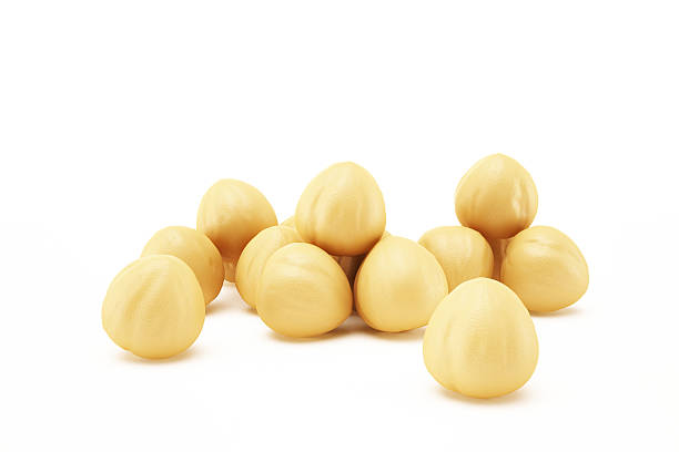 Nuts on white Macadamia nuts isolated on white background. Clipping path included macadamia nut stock pictures, royalty-free photos & images