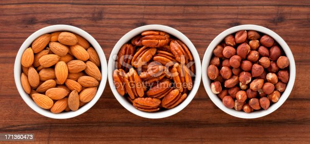 Three bowls with almonds, pecans and hazelnuts