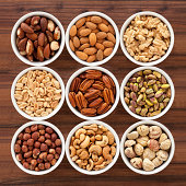 Nine bowls containing assorted nuts