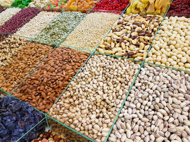 nuts, raisins, almonds counter market - nut food stock photos and pictures