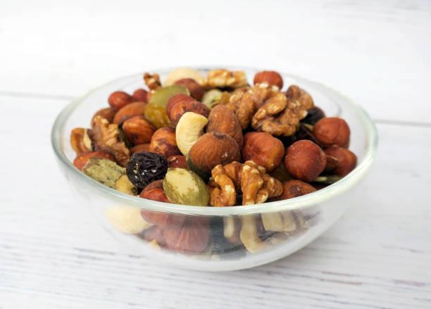 Nüsse, Samen und Trockenfrüchte in einer Glasschüssel auf einem hölzernen Lichthintergrund – Foto