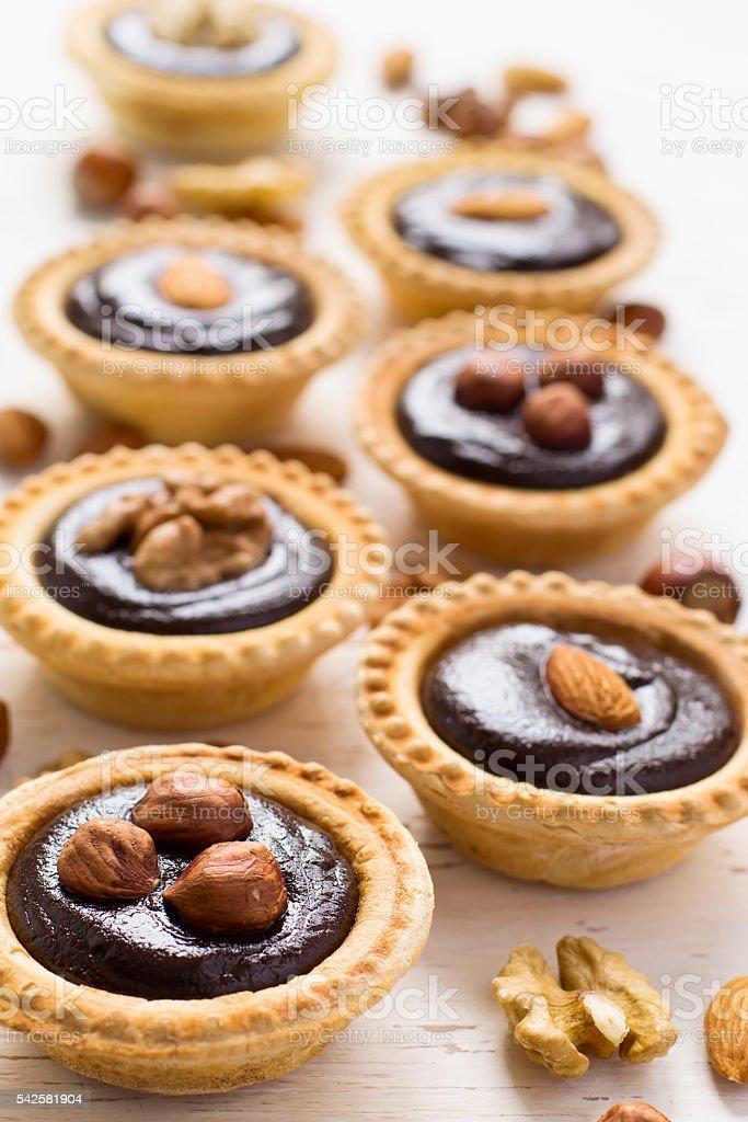 Nutty chocolate dessert small tarts on a white background - fotografia de stock
