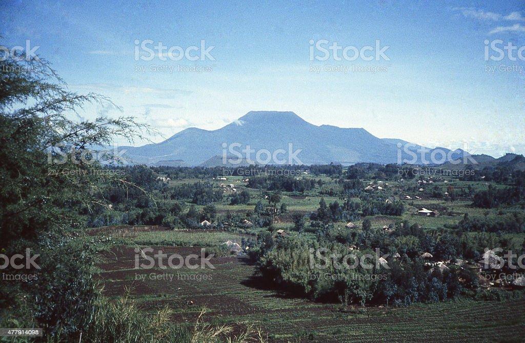 Nyiragongo Volcano Silhouette traditional village huts Mudende Rwanda DRC Congo stock photo