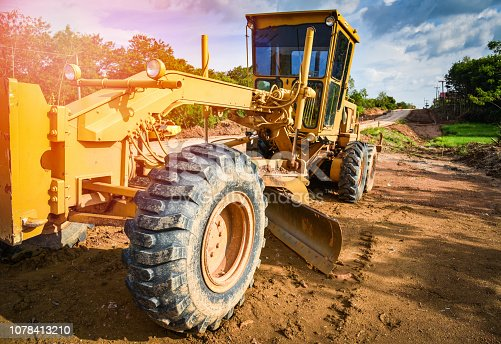 road construction with motor grader road / yellow of modern grader with wheel tractor working on construction site