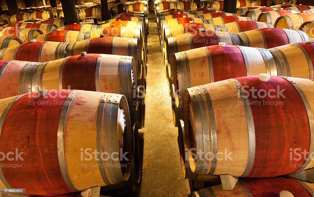 Rows of oak wine aging barrels in a winery cellar in Napa Valley,...