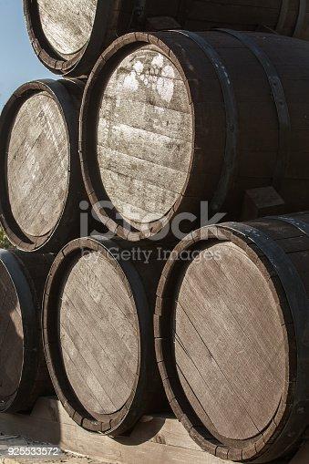 Oak wine barrels in a pile on a pallet.