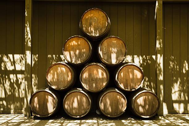 oak wine barrels stacked at winery outdoors, napa valley, california - weinkeller bauen stock-fotos und bilder