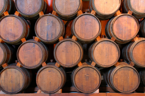 Oak wine barrels stacked in a winery cellar, Napa Valley, California, USA. Front view of old warehouse storage vessels, neatly arranged in rows for fermenting the grape alcoholic beverage. Wood is a traditional component of the winemaking industry aging process, an old-fashioned aspect of vintage varietals flavor and quality control.