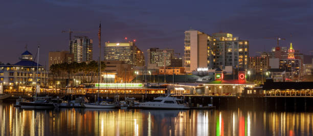 Oakland skyline at night Downtown Oakland as viewed from the Alameda side of Oakland Estuary at dusk. alameda california stock pictures, royalty-free photos & images