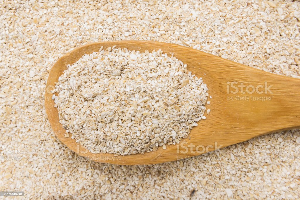Oat bran. Grains in wooden spoon. Close up. stock photo
