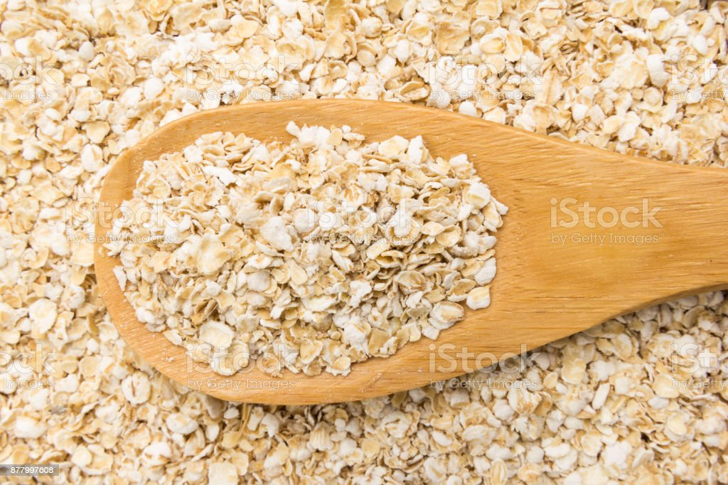 Oat cereal flake. Grains in wooden spoon. Close up. stock photo