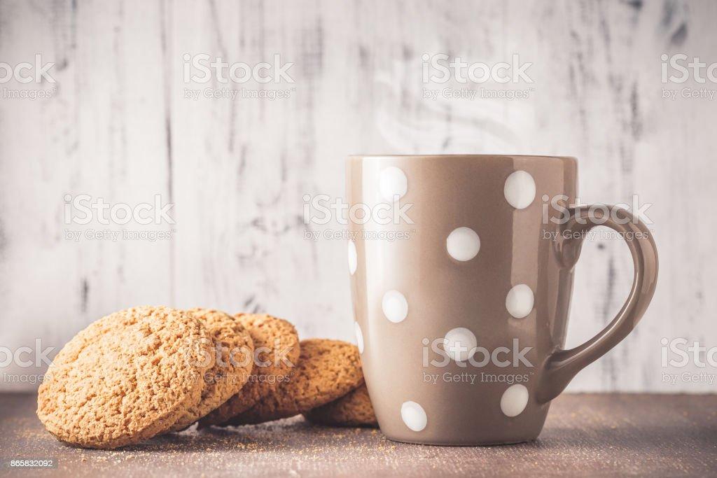 Oat cookies with mug over light wood stock photo