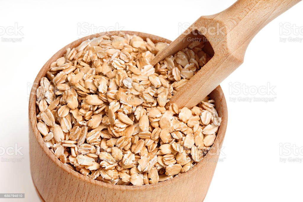 Oat flakes and scoop in wooden bowl stock photo