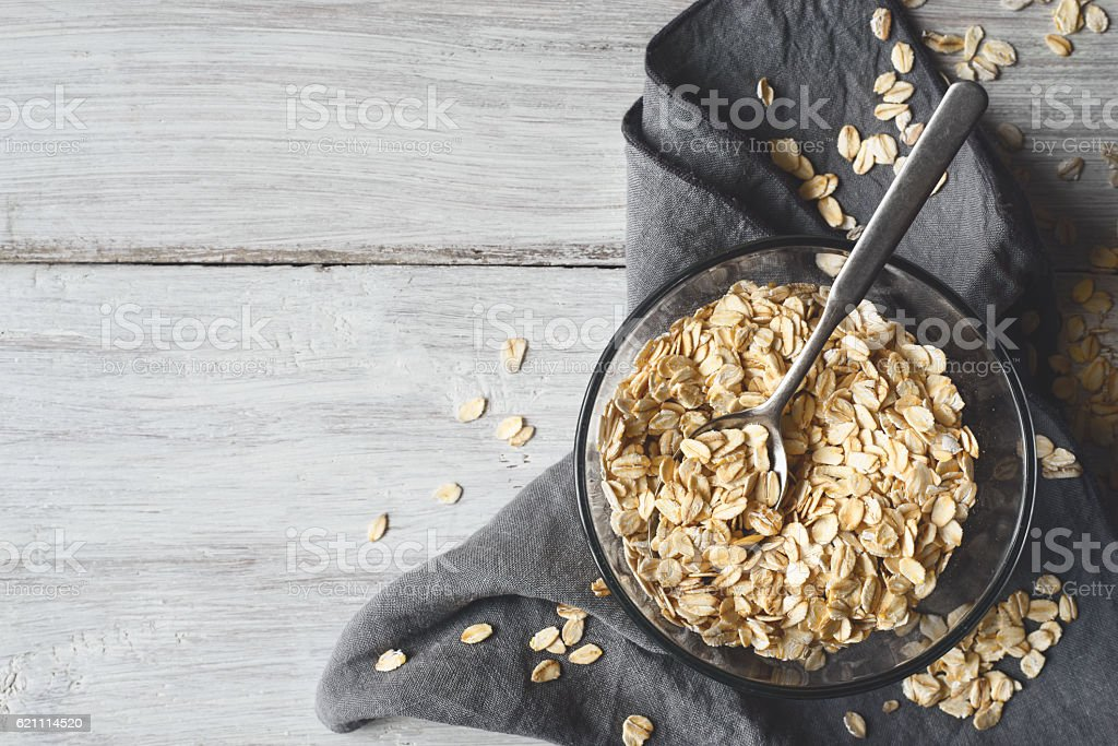 Oat flakes in a glass bowl on the wooden table – Foto