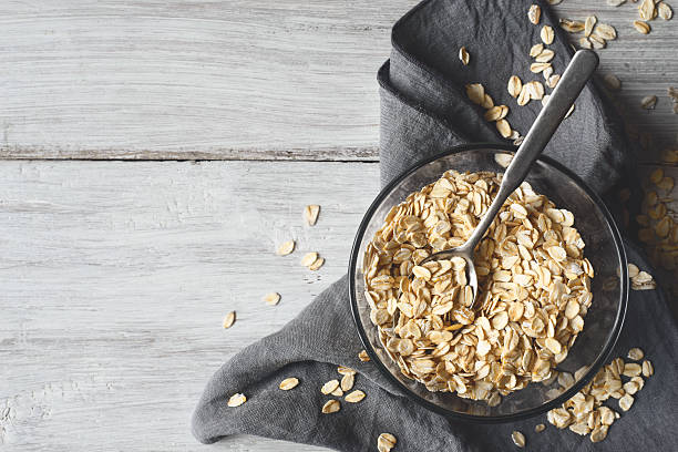 oat flakes in a glass bowl on the wooden table - oatmeal photos et images de collection
