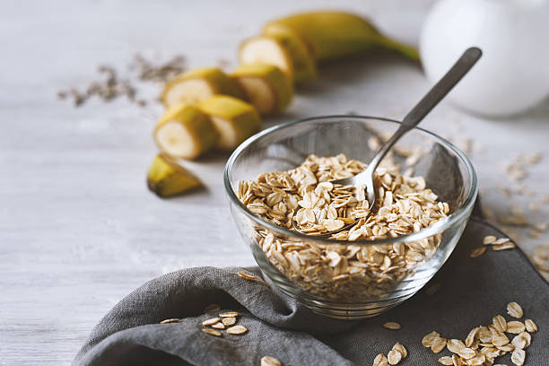 Oat flakes in a glass bowl on the wooden table stock photo
