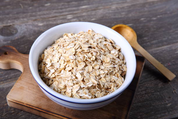 Oat flakes in a glass bowl Oat flakes in a glass bowl oatmeal stock pictures, royalty-free photos & images