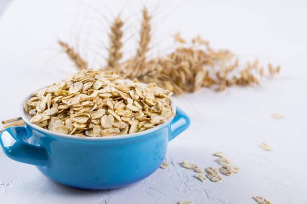 oat flakes in blue bowl on the kitchen table. healthy breakfast concept. - fotos de oats imagens e fotografias de stock