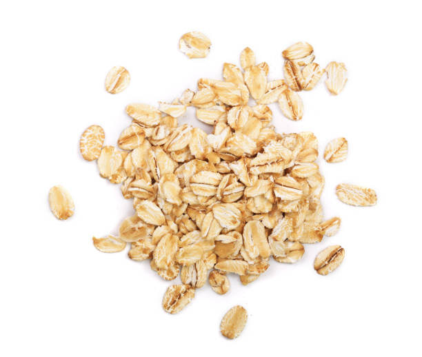oat flakes isolated on white background. top view - oatmeal stock photos and pictures
