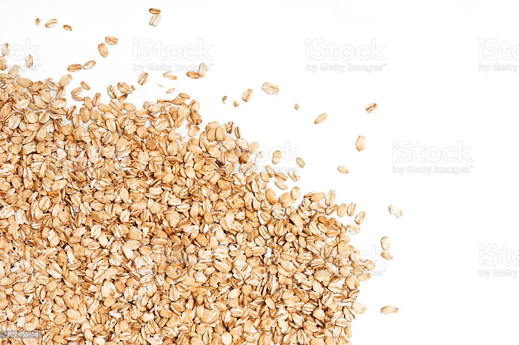 Oat flakes scattered on white background. stock photo