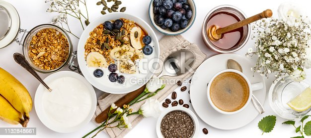599887760istockphoto Oat granola with yogurt, honey, fresh bananas, blueberries, chia seeds in bowl  and cup of coffee on white background 1132848661