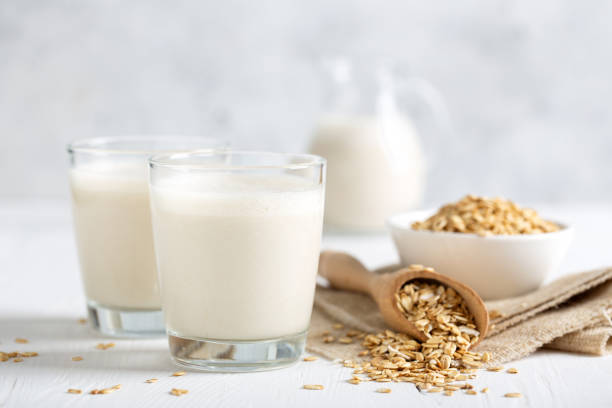Oat milk. Healthy vegan non-dairy organic drink with flakes stock photo
