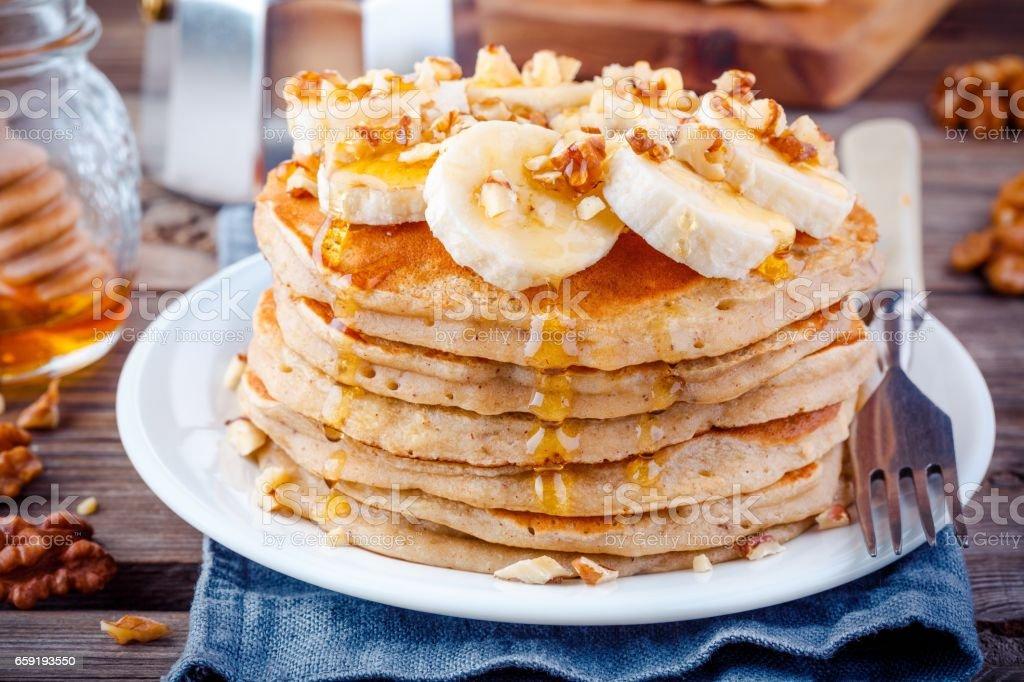 Oat pancakes with banana, walnuts and honey stock photo