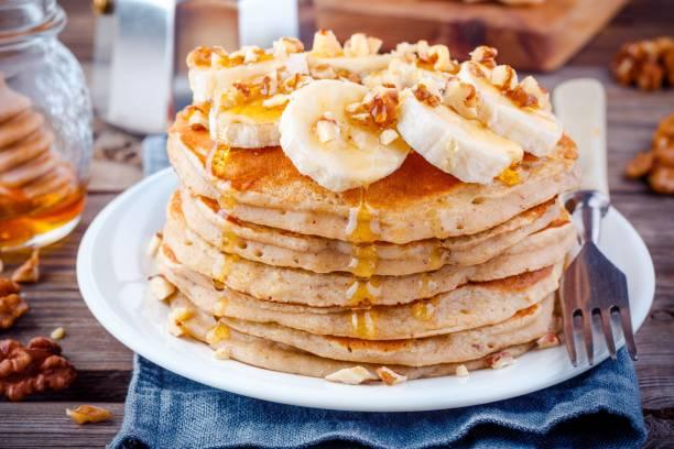 haferflocken pfannkuchen mit bananen, walnüssen und honig - gebackene banane stock-fotos und bilder