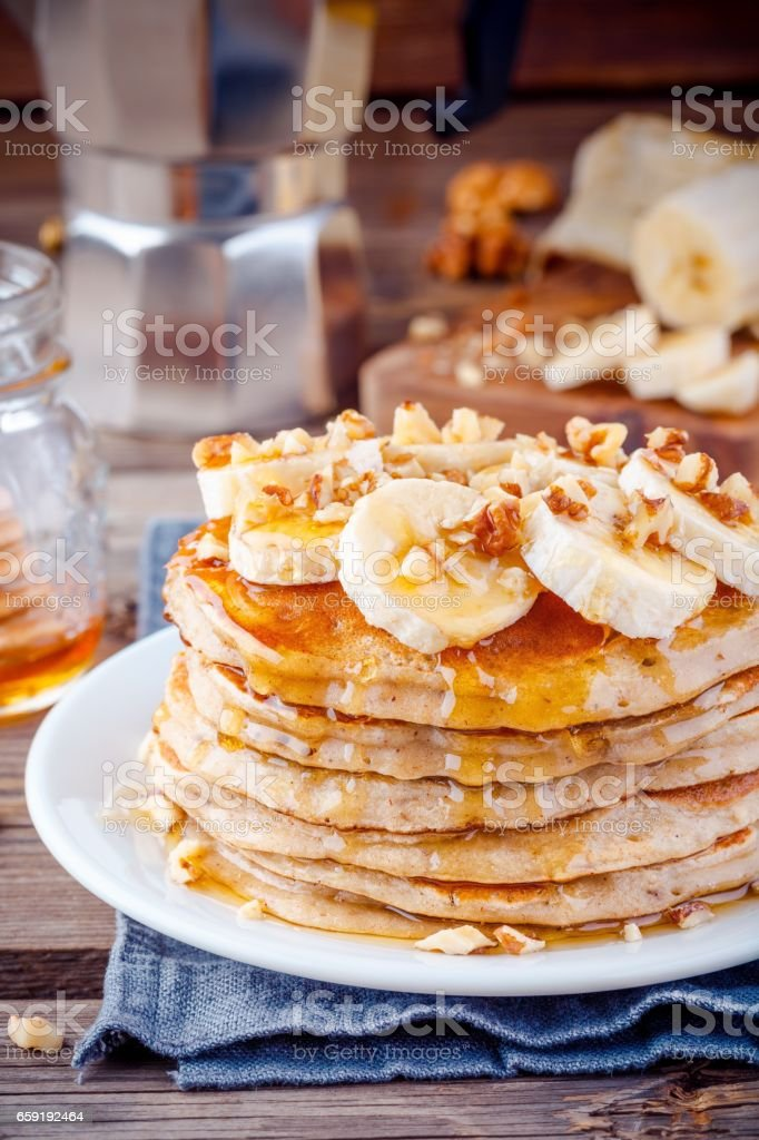 Oat pancakes with banana, walnuts and maple syrup stock photo