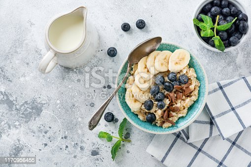 825171518 istock photo Oat porridge with banana, chocolate and fresh blueberry in a bowl on a light gray slate, stone or concrete background. Top view. 1170956455