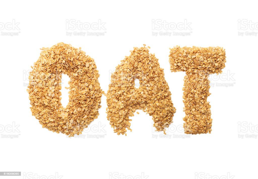 'oat' written with oat grains word. Shape of oatmeal flakes on isolated white background stock photo