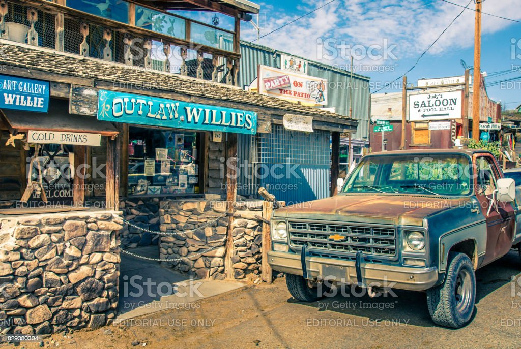 Oatman: Modern Wild West scenery with tourist shops and old rusty pickup car in Oatman. Made during a motorcycle road trip through the united states - Vintage Color Look stock photo