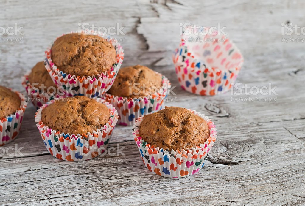 Oatmeal and banana vegan muffins on rustic light wooden board. stock photo