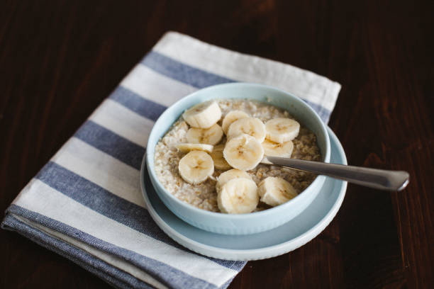 Oatmeal, banana, cream and maple syrup stock photo