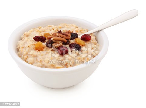 Oatmeal Bowl with dried fruits, nuts and spoon isolated on white (excluding the shadow)