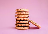 Chocolate chip biscuits are lying in a stack on a pink background