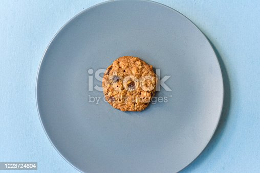 A group of baked oatmeal raisin cookies on a parchment sheet