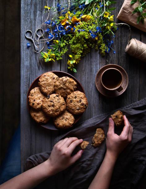 haferkekse aus vollkornmehl auf einem holztisch im rustikalen stil. weibliche hände halten ein cookie und eine tasse tee. ein bouquet von wildblumen auf dem tisch. sommerlaune. - low carb kekse stock-fotos und bilder