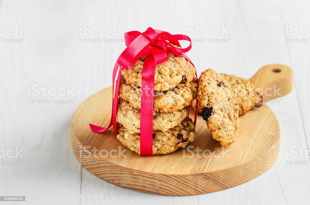 Oatmeal Cookies in gift ribbon on a wooden light background stock photo