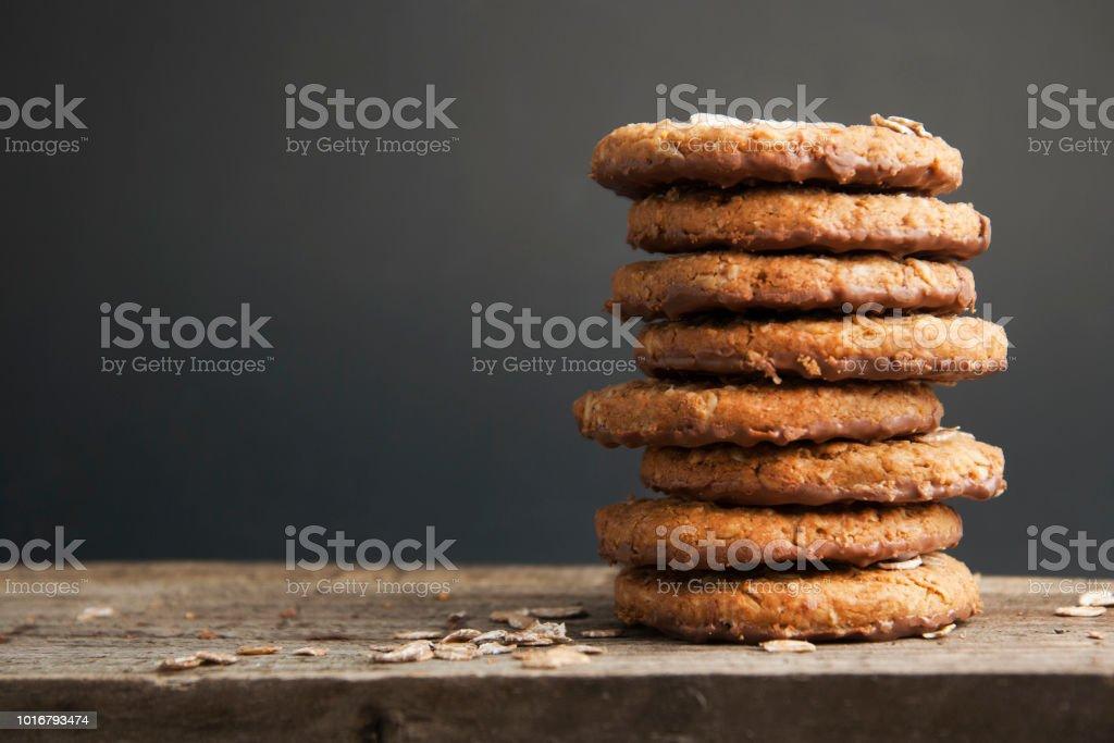 오트밀 쿠키 또는 귀리, 견과류, 계란, 검은 배경으로 갈색 어두운 woodenboard에 밀가루 비스킷 측면 보기. - 로열티 프리 갈색 스톡 사진