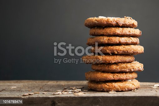 Oatmeal cookies or biscuits with oats, nuts, eggs and flour on brown dark woodenboard with black background, isolated.