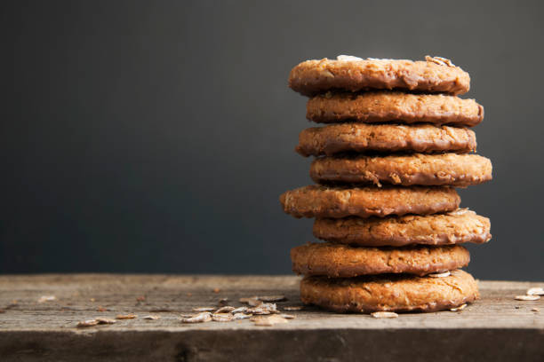 Oatmeal cookies or biscuits with oats, nuts, eggs and flour on brown dark woodenboard with black background, side view. Oatmeal cookies or biscuits with oats, nuts, eggs and flour on brown dark woodenboard with black background, isolated. biscuit stock pictures, royalty-free photos & images