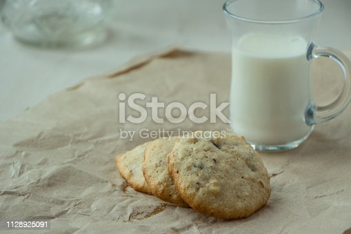 Oatmeal cookies with a glass of milk, light and white photography in a rustic style, village and countryside wooden theme