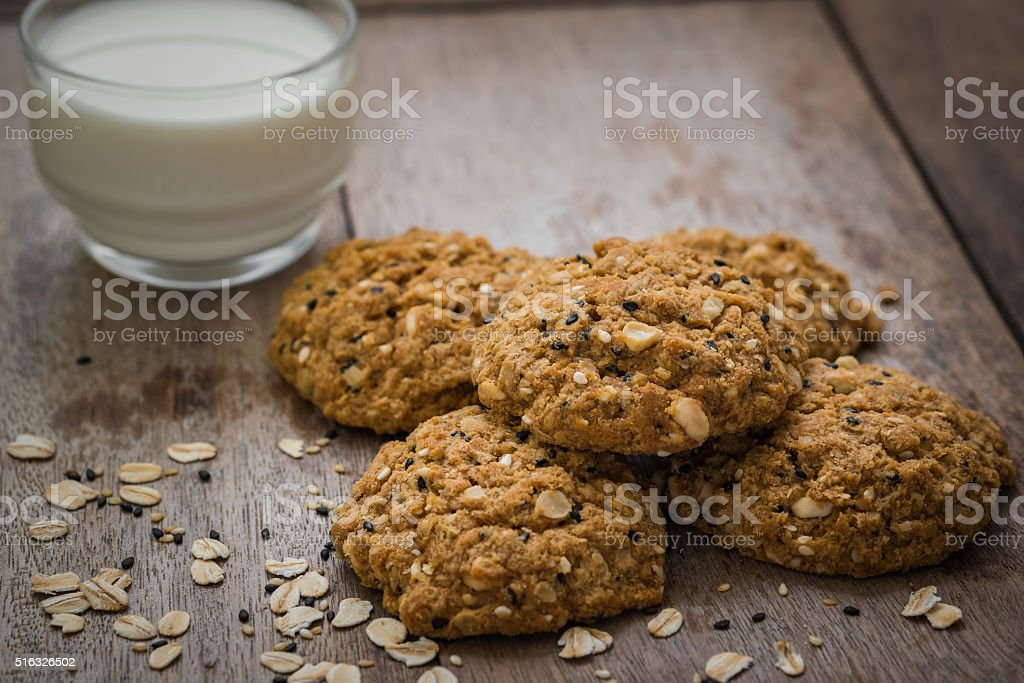Oatmeal cookies with sesame seeds and glass of milk stock photo