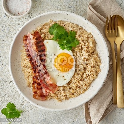 Oatmeal, fried egg, fried bacon. Hearty fat high-calorie breakfast, source of energy. Balance of proteins, fats, carbohydrates. Balanced food. Intuitive conscious food, top view