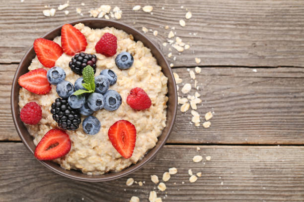 Oatmeal in bowl with berries on wooden table Oatmeal in bowl with berries on wooden table oatmeal stock pictures, royalty-free photos & images