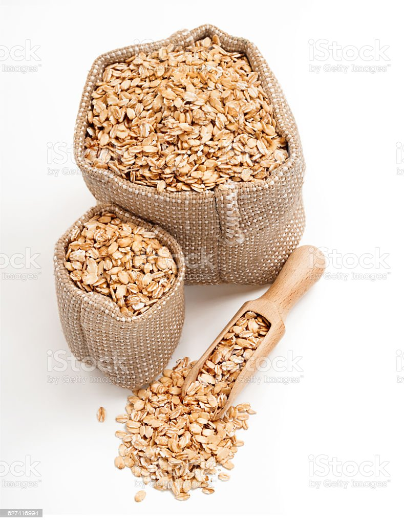 Oatmeal in burlap sack with wooden spoon stock photo