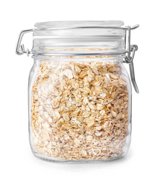 oatmeal in glass jar isolated on white - getreidebrei stock-fotos und bilder