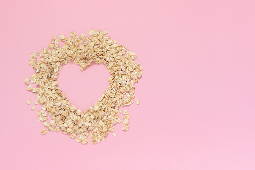 istock Oatmeal in shape of heart with empty space for text on pink background. Diet concept, Top view Copy space 1083762502