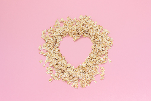 istock Oatmeal in shape of heart with empty space for text on pink background. Diet concept, Top view Copy space 1083762506